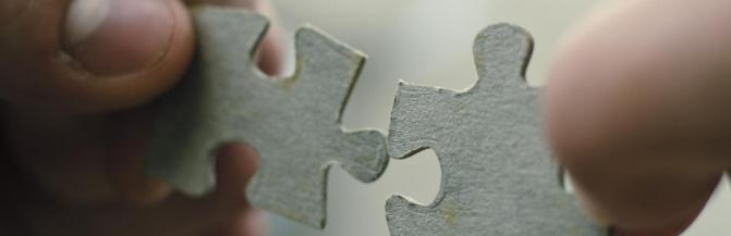 hands holding two puzzle pieces