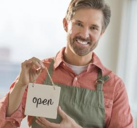 Entrepreneur standing with an Open sign